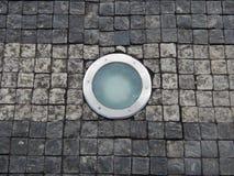 Luz de Roung en un pavimento de la piedra del adoquín Foto de archivo libre de regalías