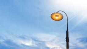 Luz de rua antiga iluminada com um alargamento brilhante do céu azul e da lente no fundo fotos de stock