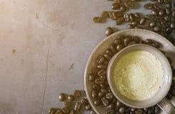 Luz de Sun da manh? Copo de café do cappuccino ou do latte com feijões de café, fotos de stock