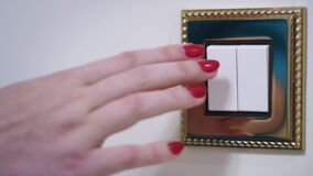Luz de torneado de la mano de la mujer apagado en la pared blanca en interior acogedor del sitio almacen de video