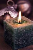 Luz de una vela con la chuchería Imagen de archivo libre de regalías