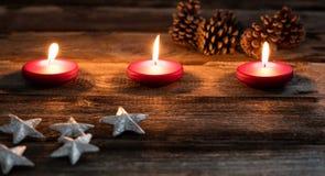 Luz de una vela de la Navidad con las velas rojas que brillan intensamente en el papel pintado de madera viejo Imagen de archivo libre de regalías