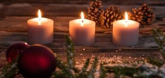 Luz de una vela del invierno de la Navidad con las velas y el bulbo del árbol en la madera Imágenes de archivo libres de regalías
