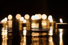Luz de vela dourada Defocused na escuridão fotos de stock royalty free