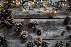 Luz decorativa de la Navidad con los conos de abeto para el fondo natural del invierno Imágenes de archivo libres de regalías