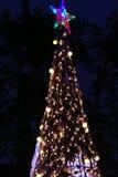Luz del copo de nieve en el árbol de navidad Fotos de archivo libres de regalías