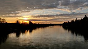 Luz del sol con el horizonte anaranjado durante la tarde en Europa del Norte en una orilla del r?o almacen de video