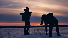 Luz del sol de la nieve de la alegría de la fotografía de la silueta del invierno de la gente grupo de turistas que caminan encim metrajes