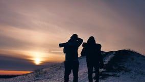 Luz del sol de la nieve de la silueta del invierno de la gente grupo de turistas que caminan encima de la montaña de la silueta d almacen de metraje de vídeo