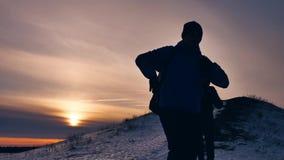 Luz del sol de la nieve de la silueta del invierno de la gente grupo de turistas que caminan encima de una montaña de la silueta  almacen de video