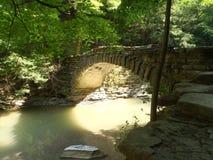 Luz del sol debajo del puente en el parque de estado pedregoso del arroyo en NY foto de archivo libre de regalías