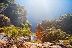 Luz del sol en las paredes del acantilado de la piedra arenisca, montañas azules foto de archivo