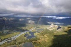Luz del sol espectacular en paisaje y el arco iris del otoño en las nubes de lluvia Foto de archivo libre de regalías