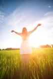 Luz del sol inferior al aire libre de la estancia de la mujer de la felicidad de la puesta del sol Imagen de archivo libre de regalías