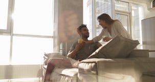 Luz del sol joven de la mañana de los pares de la raza mixta, control feliz Juice Glasses And Hispanic Man de la mujer de Asain q almacen de metraje de vídeo