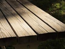 Luz del sol que golpea la esquina de una mesa de picnic Fotografía de archivo libre de regalías