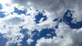 Luz del sol que viene a través de las nubes blancas y grises de la tormenta del claro, cielo azul fotografía de archivo