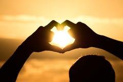 Luz del sol a través de las manos de la forma del corazón imagen de archivo