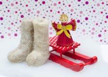 A luz diminuta sentiu botas, a decoração vermelha do Natal e o sle vermelho Fotos de Stock Royalty Free