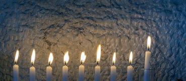 Luz do brilho das velas contra a parede textured fotografia de stock