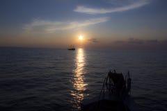 luz do por do sol do navio que navega afastado no oceano do mar aberto belamente Fotos de Stock