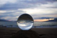 Luz do Seascape do por do sol refletida no oceano através da esfera de vidro Foto de Stock
