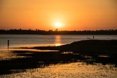 A luz do sol na noite, tem o esporte de barco do pescador dentro do rio, sol Imagens de Stock