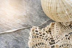 Luz - doily e agulha de crochê inacabados marrons na mesa de madeira velha Imagem de Stock Royalty Free