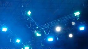 Luz e fumo do concerto na chuva Feixes amarelos e azuis brilhantes dos holofotes na fase blurry Fundo vídeos de arquivo