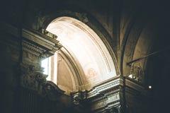 A luz está brilhando através de uma janela em uma igreja Católica histórica fotografia de stock