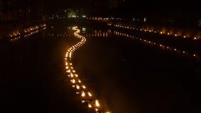 A luz forma uma serpente da luz no rio em uma noite escura imagens de stock royalty free
