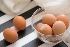 Luz fresca - ovos orgânicos marrons em uma bacia cristal pronta para a Páscoa Listras brancas e pretas como o backgroubnd para ov fotos de stock
