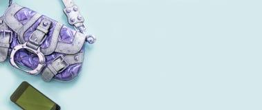 Luz moderna do dispositivo do telefone da bolsa das jovens mulheres dos acessórios de forma da bandeira - espaço azul da cópia do imagens de stock royalty free