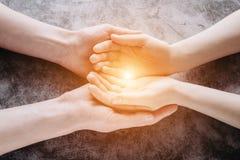 Luz nas mãos novas da família que oferecem o símbolo da ajuda, da proteção e do apoio imagem de stock