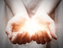 A luz nas mãos da jovem mulher. Partilha, doação, oferecendo, proteção Imagem de Stock