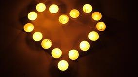 Luz que riela de velas Velas de fondo que centellea Velas ligeras del té que forman la forma de un corazón Concepto del tema del  metrajes