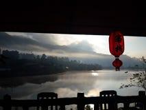 Luz roja del sytle chino y opinión del lago por la mañana en el pueblo tailandés de Rak de la prohibición, Mae Hong Son, Tailandi Imagenes de archivo