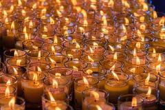 Luz rojo-anaranjada hermosa de muchas velas de la adoración Imagen de archivo libre de regalías