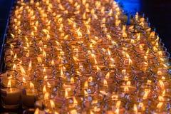 Luz rojo-anaranjada hermosa de muchas velas de la adoración Fotografía de archivo libre de regalías