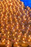 Luz rojo-anaranjada hermosa de muchas velas de la adoración Imagen de archivo