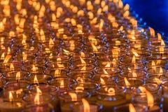 Luz rojo-anaranjada hermosa de muchas velas de la adoración Fotografía de archivo