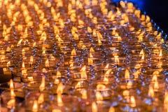 Luz rojo-anaranjada hermosa de muchas velas de la adoración Foto de archivo
