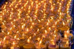 Luz rojo-anaranjada hermosa de muchas velas de la adoración Fotos de archivo libres de regalías