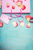 Luz - saco de compras de papel cor-de-rosa com pétala das flores e etiqueta vazia no fundo chique gasto de turquesa azul, vista s Fotos de Stock