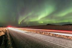 Luz septentrional sobre el camino en el camino de Noruega A muy en Escandinavia con una iluminación ligera septentrional espectac imagen de archivo