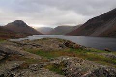 A luz solar cai em um lado da montanha do distrito do lago fora de um céu nublado ajustado contra o lago e o vale escuros, Cumbri foto de stock