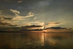Luz solar do por do sol no céu nebuloso acima da superfície da água Fotografia de Stock Royalty Free
