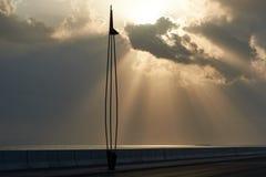 A luz solar irradia o estouro através das nuvens sobre ao mar abaixo Imagens de Stock