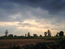 A luz solar perfura as nuvens para criar a iluminação temperamental em um cais da pesca no crepúsculo Imagens de Stock