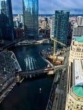 A luz solar pinta testes padrões no Chicago River nos testes padrões de arquitetura da cidade circunvizinha, porque um barco viaj Fotografia de Stock Royalty Free